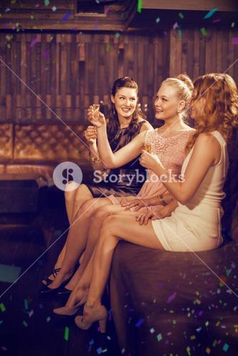Composite image of three female friends having tequila in bar