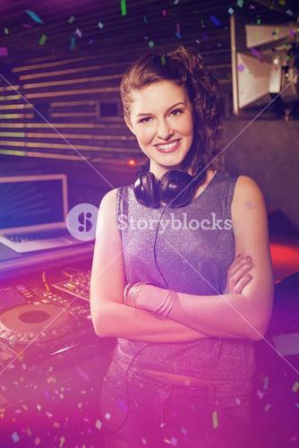 Composite image of pretty female dj standing with arms crossed