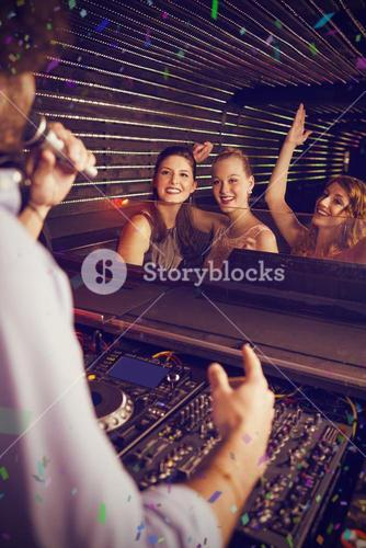 Composite image of male disc jockey playing music with three women dancing on the dance floor