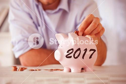 Composite image of change being put into piggy bank