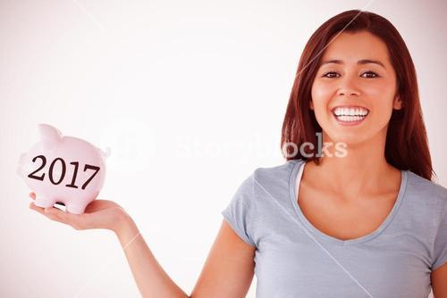 Composite image of beautiful female holding a piggy bank