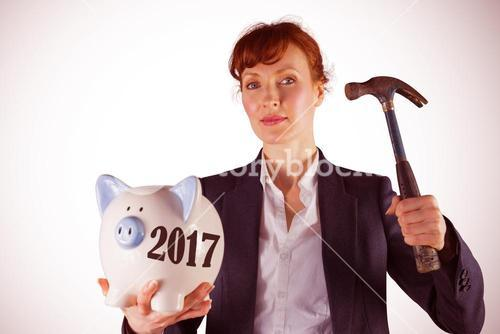 Composite image of businesswoman breaking piggy bank