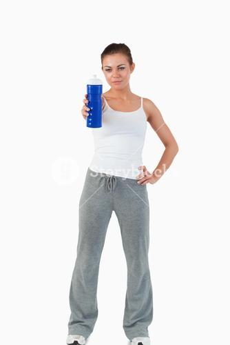 Sportswoman with hand on her hip offering a sip of water