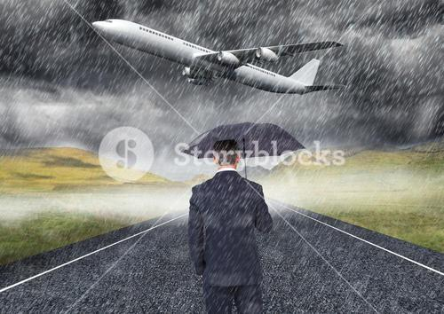 man under the rain in front of plane