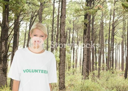 Smiling volunteer in front of forest