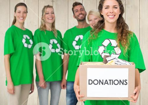 Smiling volunteer team with donation box against wooden background