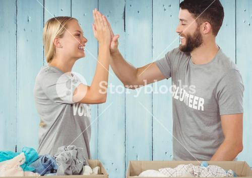 Couple of volunteer claping hand against wooden background