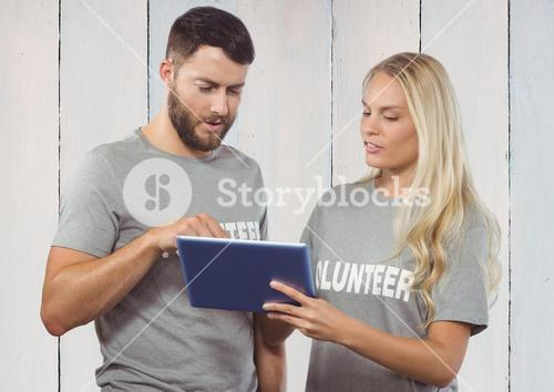 Working couple of volunteer against wooden background