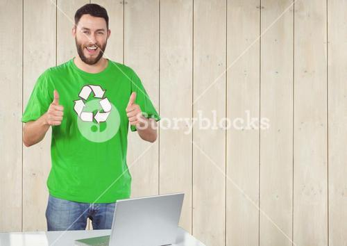 Volunteer thumbs up with computer against wooden background