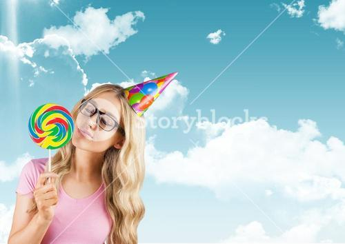 Smiling woman holding lollipop against sky background