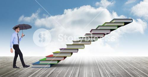 Man with umbrella climbing stairs against sky background