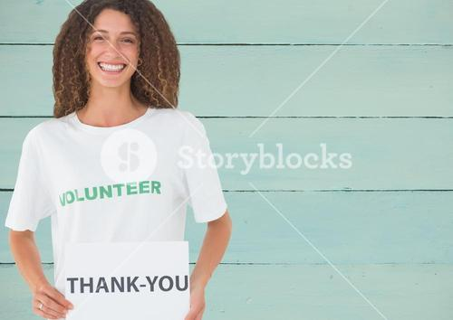 Smiling volunteer showing thanking card against wooden background
