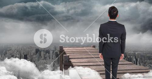 Businessman standing in front of cliff against city background