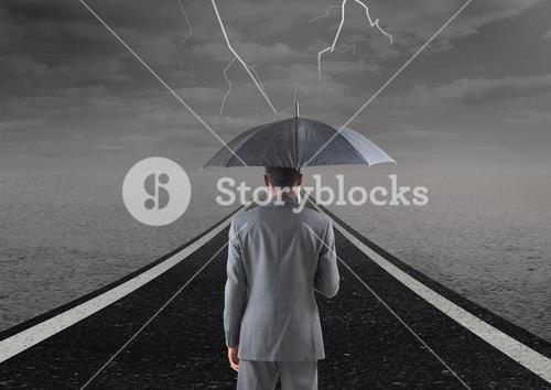 Businessman with umbrella against stormy road background