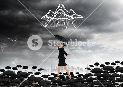 Businesswoman with umbrella against stormy background