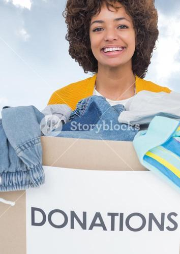 Smiling woman with donation box against sky background