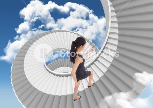 Businesswoman climbing stairs against sky background