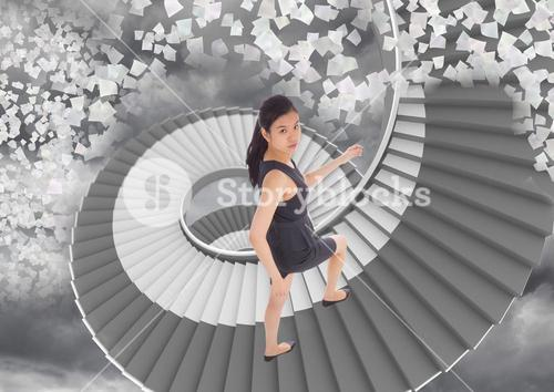 Businesswoman climbing stairs against cloudy background