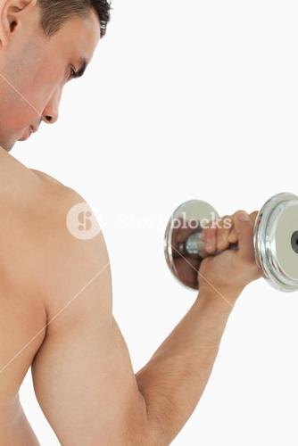 Atletic guy lifting dumbbell