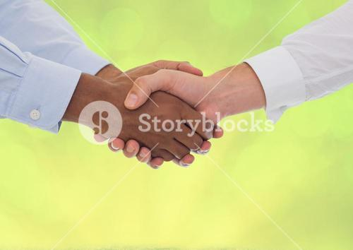 Handshake in front of green grass