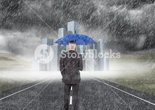 Businessman with umbrella under the rain