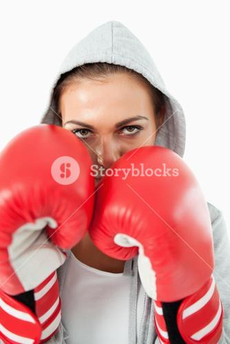 Female boxer with hoodie on in defensive stance