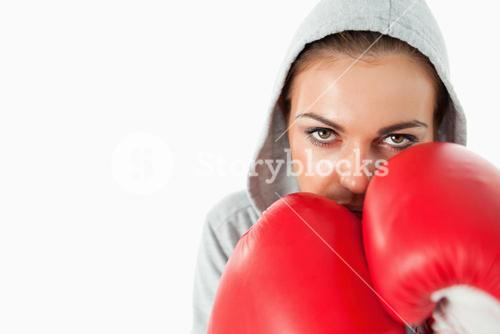 Female boxer with hoodie on in defensive position