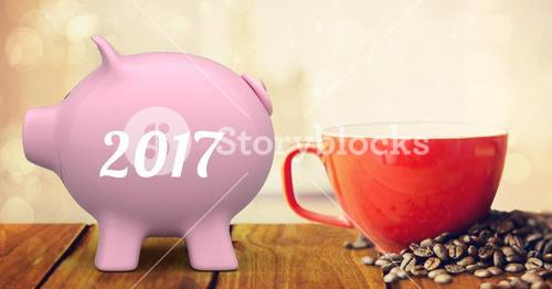 Digital composite of piggy bank with 2017