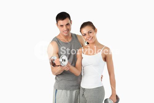 Man helping a gorgeous woman to work out