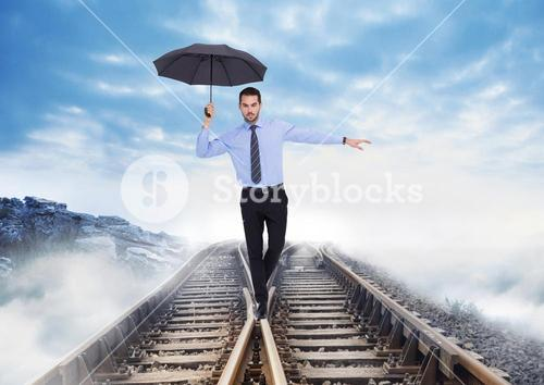 Composite of business man balancing on rails