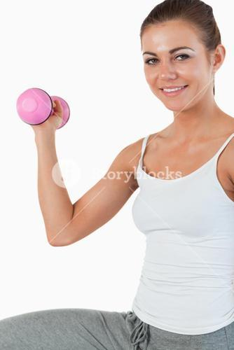 Close up of a young woman working out with dumbbells
