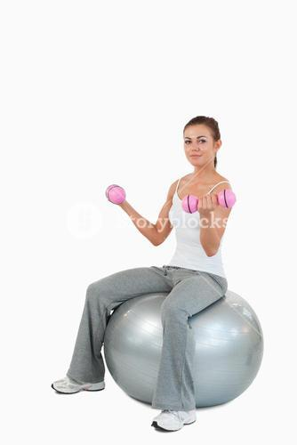 Portrait of a woman working out with dumbbells and a ball