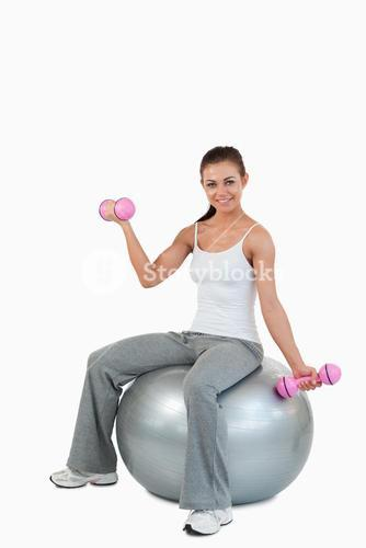 Portrait of a smiling woman working out with dumbbells and a ball