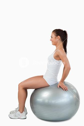 Portrait of a joyful woman working out with a ball