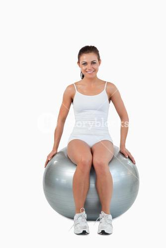 Portrait of a happy woman working out with a ball