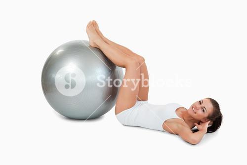 Young woman developing her abs with a ball