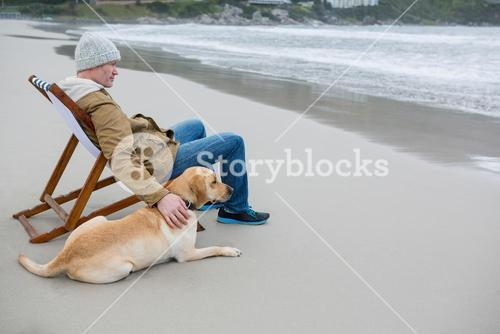 Man pampering dog while sitting on chair