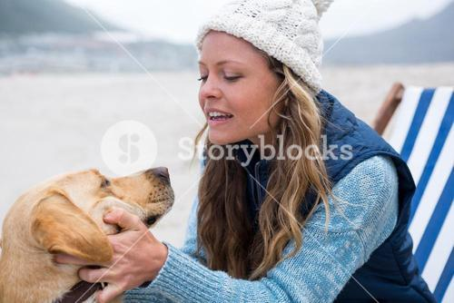 Woman pampering dog while sitting on chair