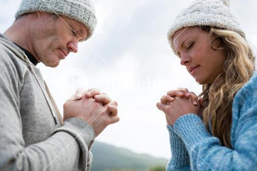 Couple praying with hands clasped