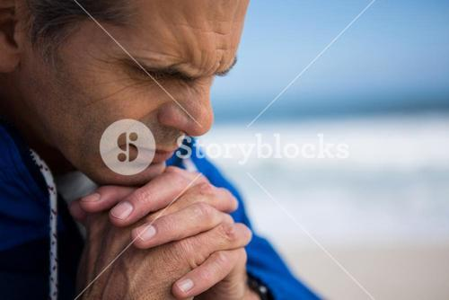 Mature man praying with hands clasped
