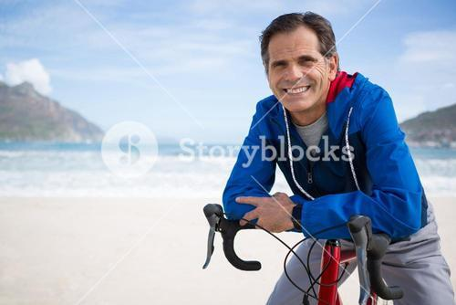 Portrait of man leaning on bicycle