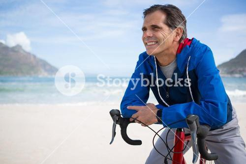 Smiling man leaning on bicycle