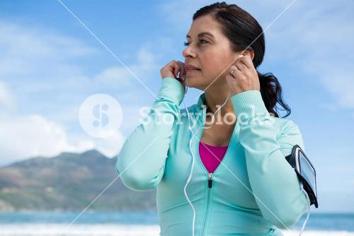 Thoughtful woman listening to music on headphones
