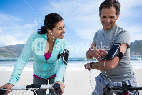 Couple leaning on bicycle while using mobile phone