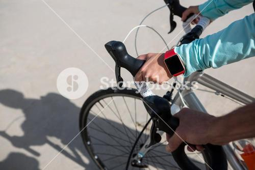 Close-up of couples hand wearing smartwatch while riding bicycle