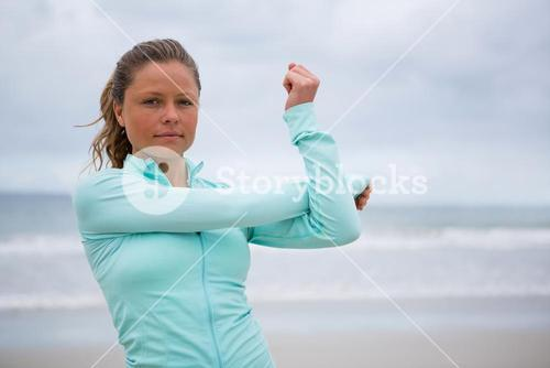 Portrait of woman performing stretching exercise on beach
