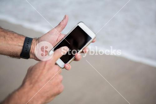 Close-up of mans hands using mobile phone