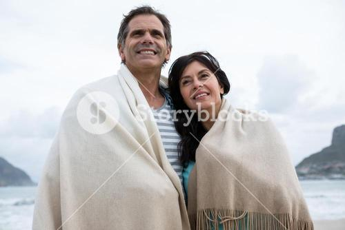 Couple wrapped in shawl on beach