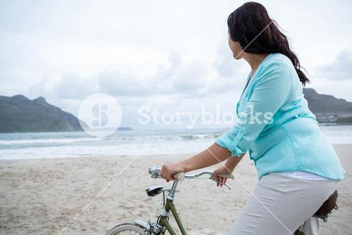 Woman standing with bicycle on beach