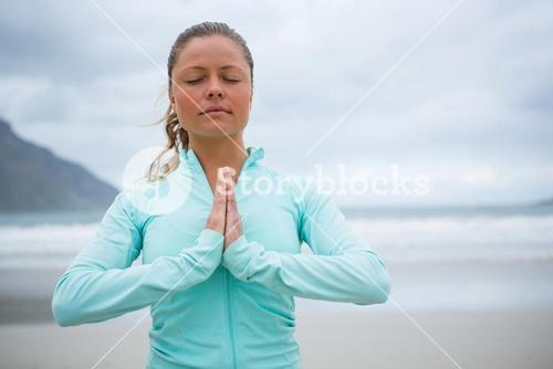 Woman performing yoga on beach